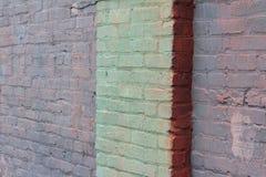 Parede de tijolo velha pintada nas máscaras do rosa verde, roxo, e salmon com uma coluna Fotografia de Stock Royalty Free