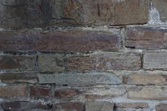 A parede de tijolo velha textured pedras escuras de tijolos diferentes das cores com cimento fotos de stock