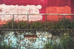Parede de tijolo vermelha e azul com um corrimão do ferro fotografia de stock royalty free