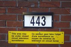 A parede de tijolo vermelho amarela brilhante do sinal da fiscalização numera Imagens de Stock Royalty Free