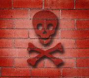 A parede de tijolo vermelho com cruz desossa grafittis imagens de stock royalty free