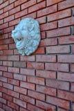 Parede de tijolo vermelho com Lion Face Sculpture fotografia de stock royalty free