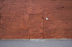 Parede de tijolo vermelho com a tira do asfalto e da porta Fotos de Stock Royalty Free