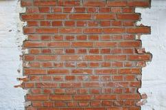 Parede de tijolo vermelho emplastrada em parte com emplastro branco imagens de stock