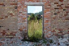 Parede de tijolo vermelho de ruínas da casa com quadro de madeira em vez das portas de madeira que servem agora como a moldura pa foto de stock