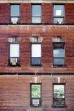Parede de tijolo vermelho velha com as janelas e os condicionadores de ar do retângulo montados em Montreal, Canadá foto de stock