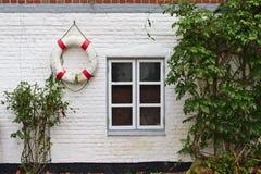 Parede de tijolo Whitewashed com janela, os arbustos verdes e a boia de vida vermelha e branca imagens de stock royalty free