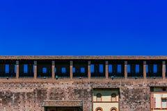 Parede do castelo de Sforzesco sob o céu azul em Milão do centro, Itália imagens de stock