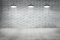 Parede do grunge do tijolo da sala e assoalho brancos da madeira com lâmpada do teto Foto de Stock