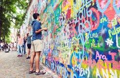 Parede dos grafittis da pintura do homem novo foto de stock royalty free
