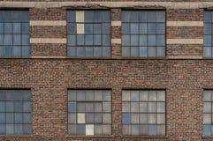 parede e janelas velhas da fábrica do tijolo na cidade Fotografia de Stock