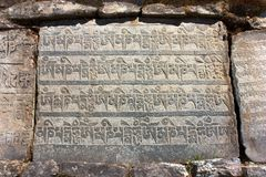Parede e pedras de Mani com símbolos budistas Fotos de Stock Royalty Free