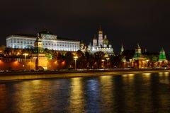 Parede e torres do Kremlin de Moscou em um fundo do palácio e de catedrais grandes do Kremlin na noite com iluminação foto de stock