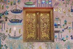 A parede exterior com mosaico e ouro bonitos pintou a janela do pavilhão no templo da tanga de Xieng em Luang Prabang, Laos Foto de Stock