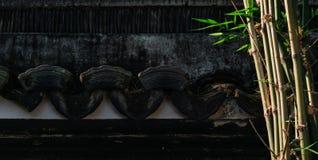 Parede preta da textura chinesa velha com as plantas de bambu no jardim chinês, jardim com fundo de construção antigo imagens de stock royalty free