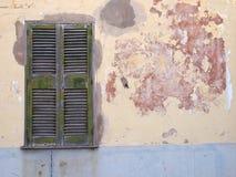 Parede rachada velha da casa com o cimento remendado pintado em camadas de descascamento de lasca de pintura amarela e vermelha c imagens de stock royalty free
