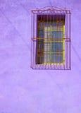 Parede roxa pintada do estuque com janela barrada Imagens de Stock Royalty Free