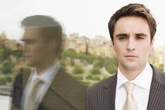 Parede segura de Standing By Glass do homem de negócios Imagem de Stock