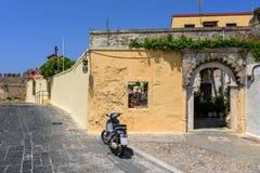 Parede velha com arco e 'trotinette' de motor estacionado na rua da cidade do Rodes Console do Rodes, Greece Fotografia de Stock