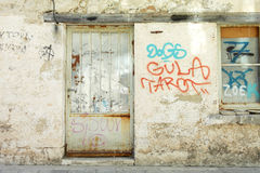 Parede velha dos grafittis com porta e janela do metal Fotografia de Stock Royalty Free