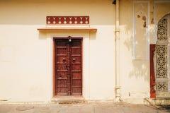 Parede velha e porta de madeira no palácio da cidade em Jaipur, Índia imagens de stock