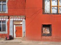 Parede vermelha da casa velha da argila com quadros de janela de madeira do vintage, as portas vermelhas de madeira e as cortinas Imagens de Stock