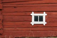 Parede vermelha de madeira velha do log com a janela pequena, tradicional em Escandinávia fotografia de stock royalty free