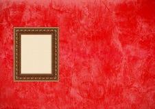 Parede vermelha do estuque de Grunge com frame de retrato vazio Foto de Stock