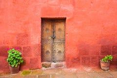 Parede vermelha e porta de madeira velha Foto de Stock Royalty Free