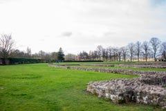 Paredes de piedra en un parque con los árboles desnudos y la hierba verde, Reino Unido Imagen de archivo libre de regalías