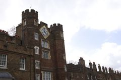 Paredes de tijolo de Brown com um pulso de disparo dourado dentro e o céu nebuloso em Londres imagem de stock royalty free