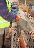 Paredes de tijolo da construção do trabalhador no canteiro de obras da casa, no pedreiro e no cimento Imagem de Stock