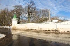 Paredes del monasterio con una torrecilla a lo largo del camino Foto de archivo