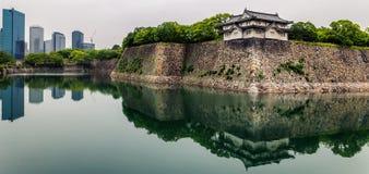 Paredes do castelo de Osaka e prédios de escritórios modernos com reflexões no fosso foto de stock