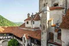 Paredes e torres do castelo do farelo e das montanhas Carpathian ensolaradas A residência legendária de Drakula nas montanhas Car foto de stock royalty free