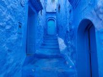 Paredes, escaleras y puertas azules del callejón de Medina de Chefchaouen, Marruecos Fotografía de archivo libre de regalías