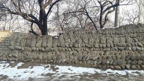 Paredes hechas de la arcilla y de las piedras en los pueblos de montaña y los pueblos Imagen de archivo libre de regalías