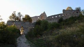 Paredes orientais e entrada principal às ruínas do castelo gótico adiantado Topolcany durante o por do sol adiantado da queda imagens de stock royalty free