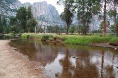 Paredes y árboles del granito que reflejan en el río de Merced Imagenes de archivo