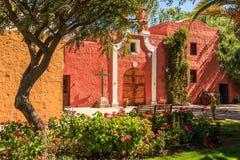 Paredes y puerta rojas de la capilla católica española con los árboles y flo Imágenes de archivo libres de regalías