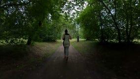 Pareggiando nella sosta Funzionamento della ragazza lungo il sentiero nel bosco Movimento lento archivi video