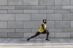Pareggiatore afroamericano che fa allungamento dopo l'allenamento di mattina Immagini Stock Libere da Diritti