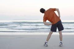 Pareggiatore che fa allungamento su una spiaggia Fotografia Stock