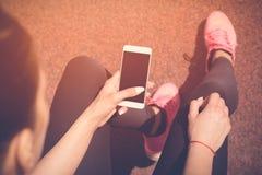 Pareggiatore che per mezzo dello smartphone sulla pista corrente Fotografia Stock
