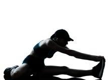 Pareggiatore del corridore della donna che allunga le gambe che si scaldano siluetta Immagine Stock