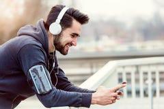 Pareggiatore dell'uomo con le cuffie facendo uso di Smartphone e di musica d'ascolto Fotografia Stock