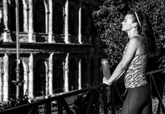 Pareggiatore della donna con la bottiglia di acqua che si rilassa dopo l'allenamento Fotografia Stock