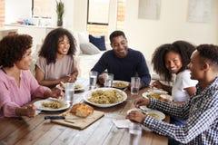 Pareja afroamericana envejecida media que se sienta en la tabla de cena que come con sus niños, cierre para arriba foto de archivo libre de regalías