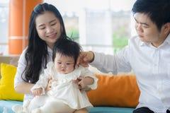 Pareja alegre y dulce de la esposa y del marido con el bebé y el hombre de la tenencia de la madre que juegan con poca hija en co imágenes de archivo libres de regalías
