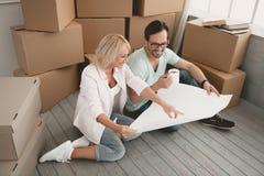 Pareja casada adulto que se sienta en el piso del apartamento imagen de archivo libre de regalías
